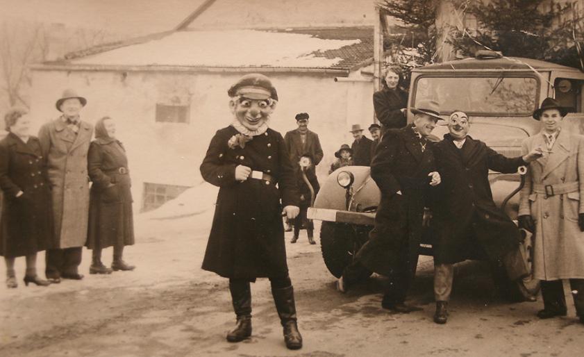 """""""Polizist"""" Toni Reuter mit Clownmaske gab den Ankündiger des Rosenmontagszuges Anfang der 1950er Jahre."""