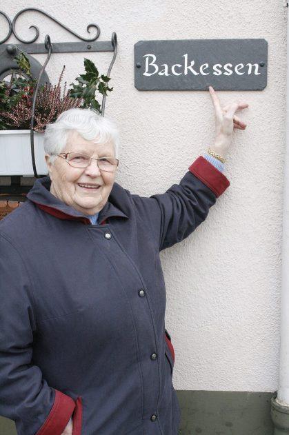"""Birresborn, Landkreis Vulkaneifel: In vielen Eifeldörfern sind die alten Hausnamen noch bekannt. Auch in Birresborn werden sie an den Fassaden der Gebäude als Identität stiftendes Detail angebracht. Hier Maria Wirtz an ihrem Wohnhaus, das immer """"Backessen"""" hieß."""