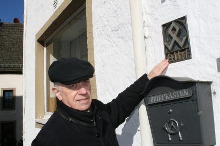 """Müllenborn, Landkreis Vulkaneifel: """"Erbhof"""": Ortshistoriker Erwin Schäfer am Hauszeichen aus der NS-Zeit in der Fassade des ehemaligen """"Coels-Hof""""."""